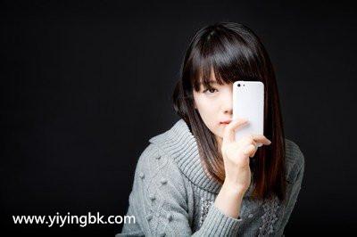 美女拿着手机挡着半边脸